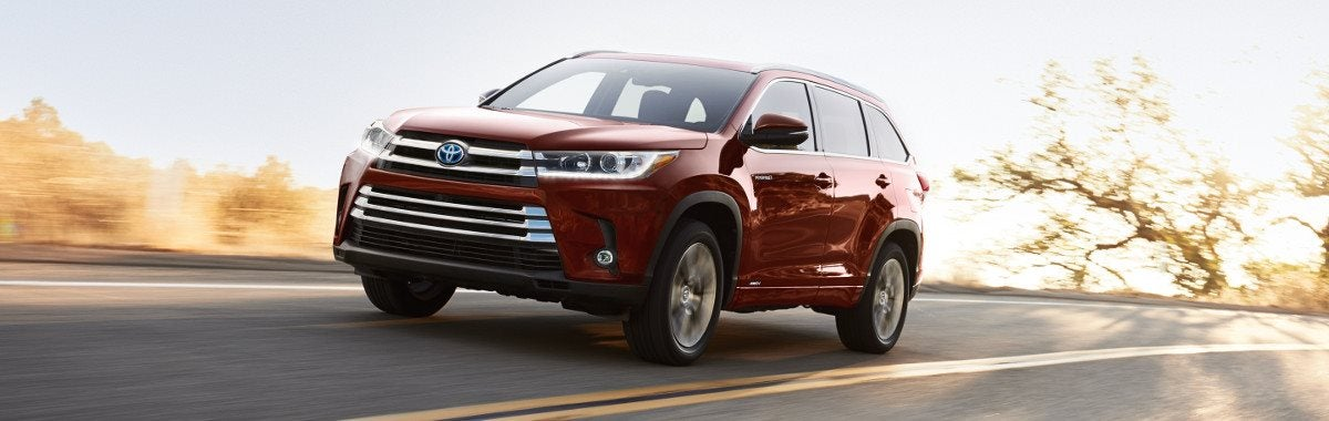 A Red 2019 Toyota Highlander Driving Down An Open Road