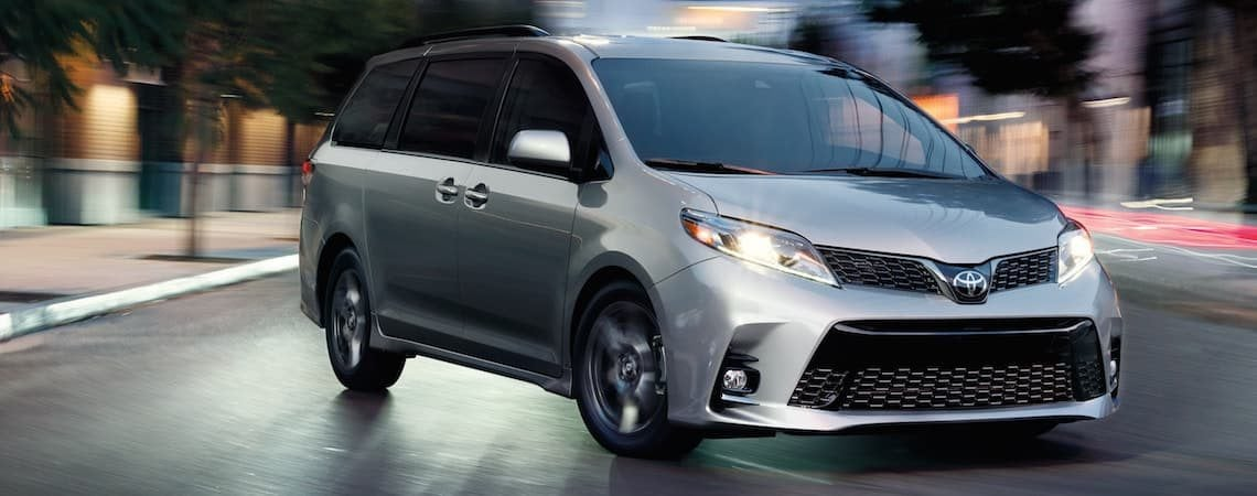 A 2019 Toyota Sienna Driving Through City At Night
